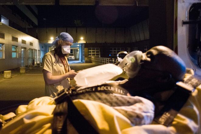 Des bénévoles de la protection civile transfèrent des patients infectés par le COVID 19 et ayant des problèmes respiratoires dans les hôpitaux parisien © AFP