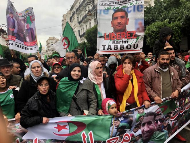 Zahra, l'épouse de Karim Tabbou, voile rose pastel et blanc, et leurs enfants ouvrent en famille le cortège de soutien appelant à la libération de son mari lors d'un vendredi de manifestation à Alger, en novembre 2019. © Kahina Nour
