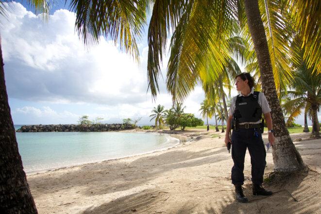 Une policière surveille la plage fermée du Gosier en Guadeloupe, le 20 mars 2020 © Cedrick Isham CALVADOS / AFP