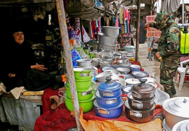Désinfection d'un marché dans le quartier de Sadr City à Bagdad, le 28 mars 2020. © Ahmad Al-Rubaye/AFP