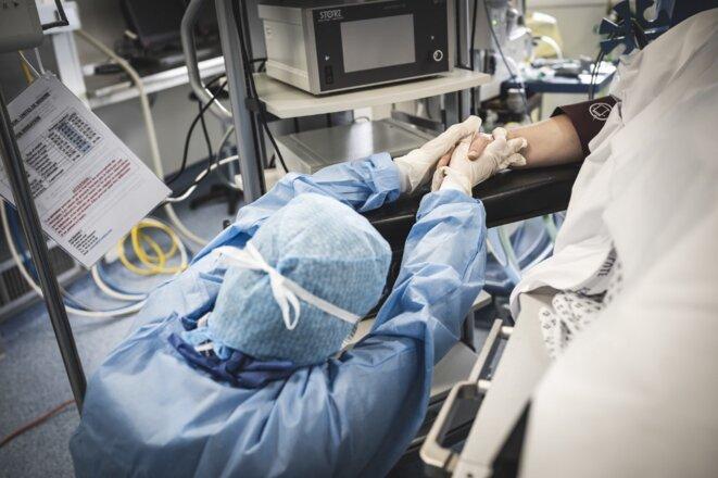 Une infirmière tient la main d'un patient en réanimation atteint du Covid-19, dans un hôpital du sud de la France. © Frédéric Dides/AFP