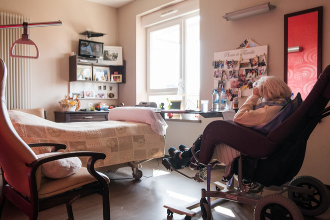 A resident reads in her room at a care home in Marchiennes, northern France, March 27th 2020; the residents are confined in their rooms to stop the virus spreading. © Julie Sebadelha /AFP