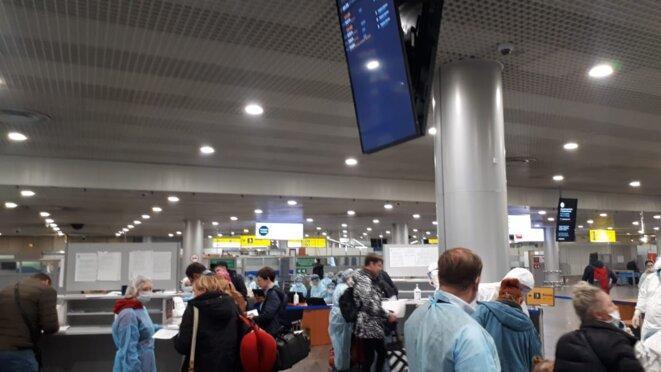 Accueil des arrivants à l'aéroport de Cheremetievo par des agents de Rospotrebnadzor, probablement inspecteurs sanitaires ou médecins de santé publique © Collection personnelle