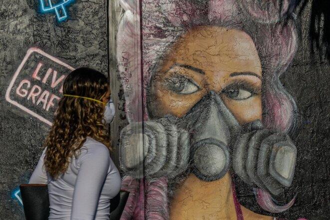 Miami (Floride), 3 avril 2020. Une femme passe devant la vitrine d'un magasin fermé. © Chandan Khanna / AFP