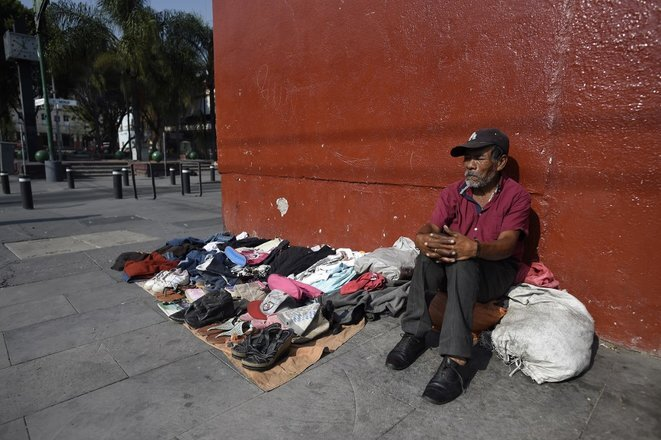 Un hombre vende ropa de segunda mano en la avenida Lázaro Cárdenas, Ciudad de México, 1 de abril de 2020. © Alfredo Estrella/AFP