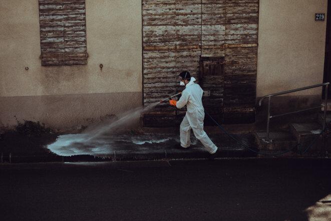 Un homme désinfecte une rue de Marseille contre la propagation du SARS-CoV-2 (Theo Giacometti/Hans Lucas via AFP).