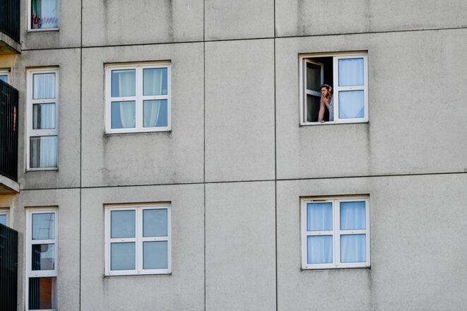 Un habitant fume à la fenêtre, à Montreuil, le 4 avril 2020 © Remi Decoster / Hans Lucas via AFP