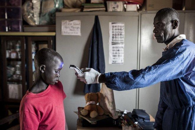 A un niño de la calle en un centro de Dakar se le toma la temperatura el 10 de abril de 2020. © John Wessels/AFP