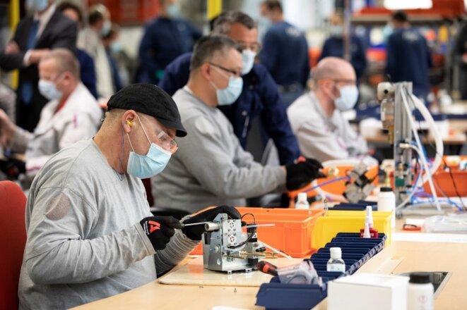 Des employés de PSA assemblent des pièces de respirateurs artificiels dans l'usine de Poissy le 15 avril 2020. © Thomas Samson/AFP