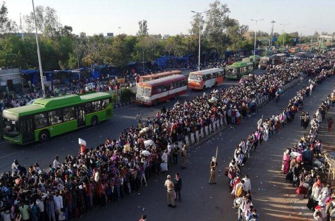 À la frontière de Delhi-UP, des milliers de travailleurs migrants tentent d'embarquer dans des bus d'État pour rentrer chez eux, le 29 mars 2020