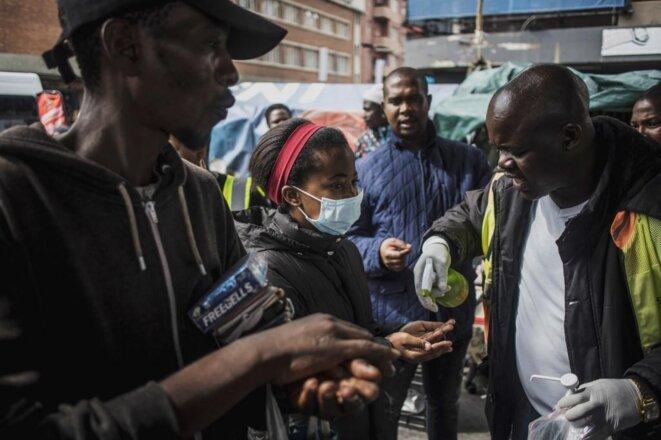 Des bénévoles distribuent du gel désinfectant contre le Covid-19 dans les rues de Johannesburg en Afrique du Sud le 18 mars 2020