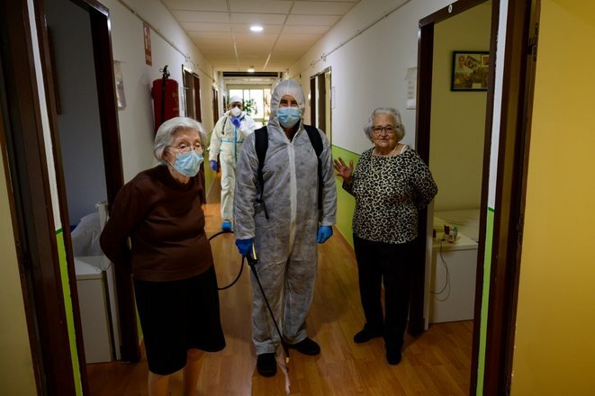 Un empleado desinfecta una residencia de ancianos en Pozuelo de Alarcón, cerca de Madrid, junto con dos residentes, 15 de abril de 2020. © AFP