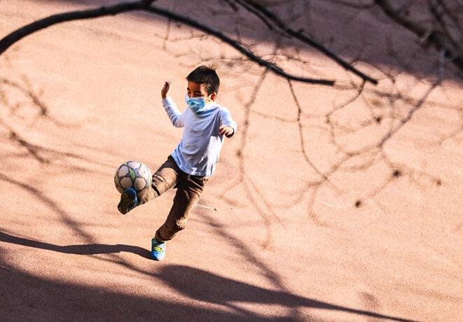Un jeune garçon jouant dans les rues de Pékin, le 22 mars | © Iconsport