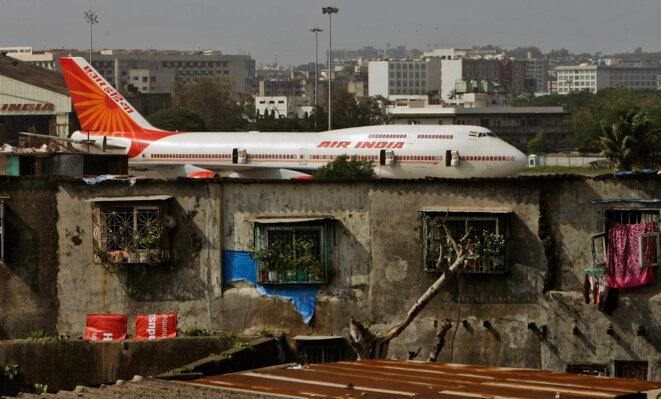 Un Boing 747 d'Air India visible depuis les taudis de Mumbai en Inde. © Rajanish Kakade - AP Photo