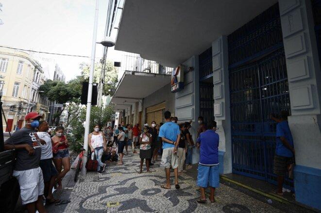 Des habitants de Recife attendent devant une banque pour recevoir une aide fédérale le 29 avril 2020. © Paulo Paiva/AGIF VIA AFP