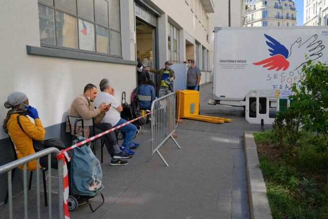 A partir de midi, les bénéficiaires de l'aide alimentaire du Secours populaire prennent place dans la file d'attente. © Antoine Peillon (Ishta)