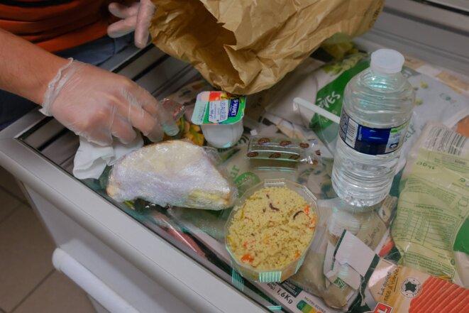 Adrien de La Sayette, 30 ans, bénévole, montre le contenu d'un repas halal type. © Antoine Peillon (Ishta)