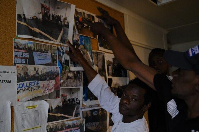 """Au squat du collectif de sans-papiers Schaeffer, Doumbia Dramane Adama et ses """"frères"""" montrent les photos de leurs manifestations pour """"obtenir des papiers"""". © Antoine Peillon (Ishta)"""