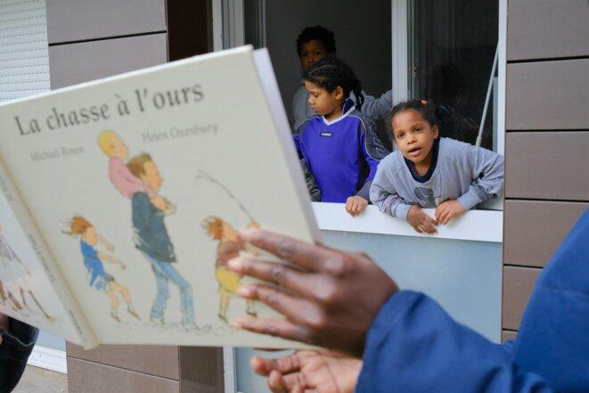 Le tandem d'ATD QM arrive devant les fenêtres de Jean-Robert et de ses quatre enfants, en rez-de-chaussée. © Antoine Peillon (Ishta)