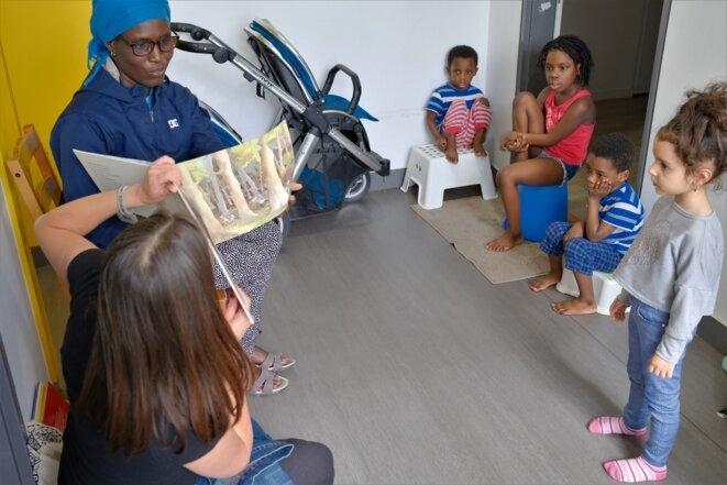 Au deuxième étage, deux familles ouvrent leurs portes au même moment. Une première maman, Bénédicte, 32 ans, originaire de Côte-d'Ivoire, pousse Leïla, 6 ans, et les jumeaux Hassan et Ouseyne, trois ans et demi, devant elle, tandis qu'elle se tient sur le seuil. Juste à côté, Stefania, 34 ans, venue de Bulgarie, laisse sortir trois fusées : Mariella, 16 ans, Emmanuella, 7 ans, et Borislava, 3 ans. © Antoine Peillon (Ishta)
