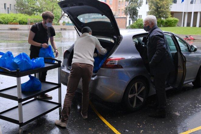 Pierre Hommey, 70 ans, est venu avec sa voiture particulière, comme chaque matin, prendre un chargement d'une trentaine de panier-repas, de bouteilles de lait et d'eau qu'il se dépêche de ramener à sa paroisse, Saint-Léon-le-Grand, dans le XVe arrondissement. © Antoine Peillon (Ishta)