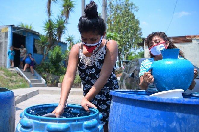Residentes de un barrio pobre de Ciudad Delgado, El Salvador, acceden gratuitamente al agua, 8 de abril de 2020. © AFP/Marvin Recinos