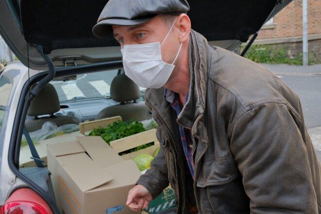 Boris Darque, bénévole des Marmoulins de Ménil', aide Laura à charger sa voiture. © Antoine Peillon (Ishta)
