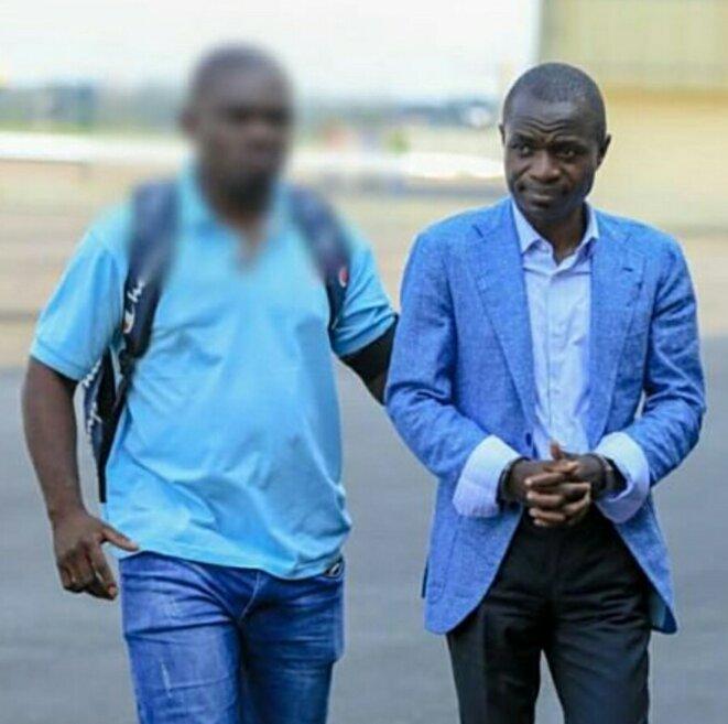 Alexis Ndouna, menottes aux poignets, lors de son extradition en décembre 2019, le début de la fin