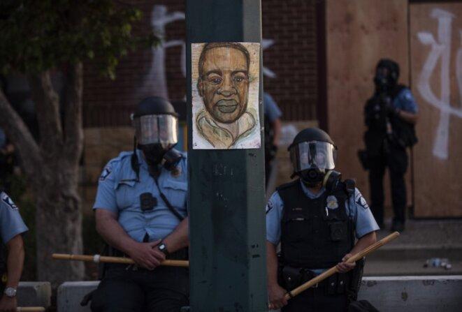 27 mai 2020, Minneapolis, États-Unis. Un portrait de George Floyd entre deux policiers durant une manifestation. © Stephen Maturen/Getty Images/AFP