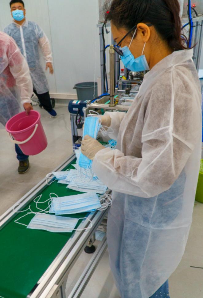 Employée faisant le tri de masques chirurgicaux en sortie de chaine © Alain Delpey