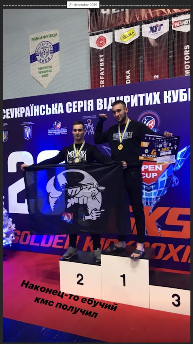 Marc de Cacqueray (à gauche) brandissant un drapeau du GUD Paris, lors d'un championnat de kick-boxing en Ukraine, le 21 décembre 2019.