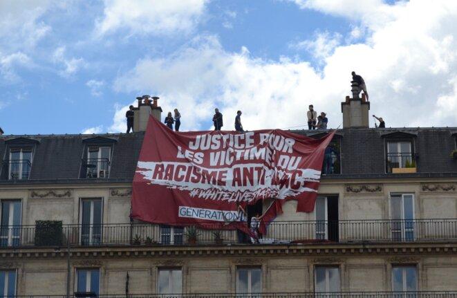 Les habitants du dernier étage déchire la banderole des militants d'extrême droite. Place de la République, Paris, 13 juin 2020. © Samuel Clauzier