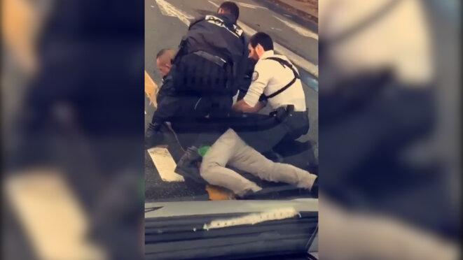 Cédric Chouviat, encore casqué, plaqué au sol, trois policiers sur lui, 3 janvier 2020, Paris. © Document Mediapart