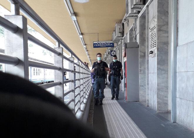 Deux policiers italiens « escortent» un jeune homme noir sur le quai de la gare de Vintimille, le jeudi 11 juin 2020. © Morgane Dujmovic