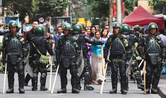 Des Ouïghours marchent près de la police tout en formant une ligne dans une rue le 8 juillet 2009 à Urumqi, la capitale du Xinjiang, en Chine. Photo de Guang Niu / Getty Images