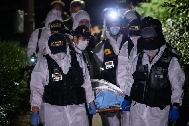 Une équipe médicolégale porte le corps du maire de Séoul, Park Won-soon, peu de temps après que les équipes de secours ont découvert son corps. Photo : ED JONES / AFP
