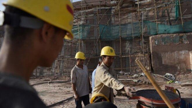 Des travailleurs préparent de l'équipement dans une section de la vieille ville de Kashgar, dans la région autonome ouïghoure du nord-ouest de la Chine, le 4 juin 2019.