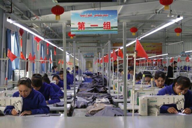 Des femmes ouïghoures travaillent dans une usine de tissus du comté de Hotan, dans la province du Xinjiang, en Chine. Près du quart du coton brut du monde est transformé en tissu au Xinjiang. Photo: Shutterstock