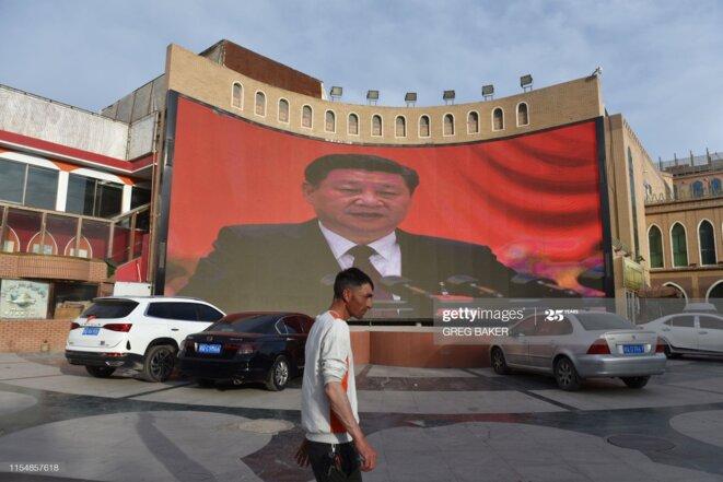 Un homme passe devant un écran montrant des images du président chinois Xi Jinping à Kashgar, dans le nord-ouest de la Chine, dans la région du Xinjiang, le 4 juin 2019. Greg Baker / AFP via Getty Images