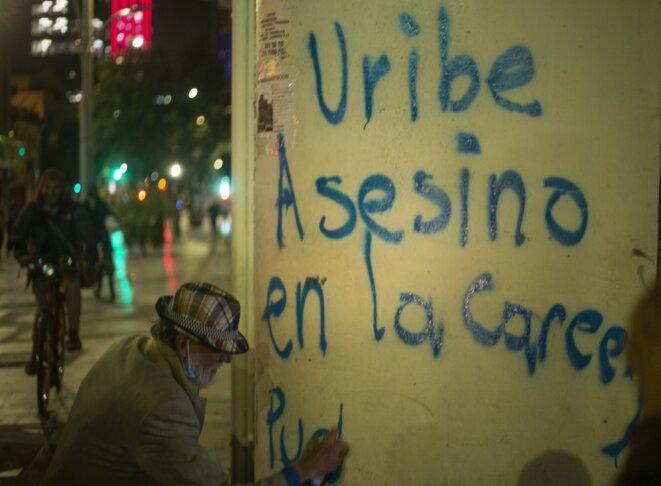 Un opposant à Alvaro Uribe écrit sur un mur de Bogota le 4 août 2020 : « Uribe assassin, en prison… » © Daniel Garzon Herazo/NurPhoto/AFP