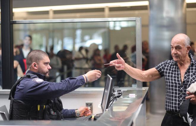 Un agent des services américains de l'immigration contrôle les documents d'un homme au San Ysidro Port of Entry le 2 octobre 2019. © Sandy Huffaker/AFP