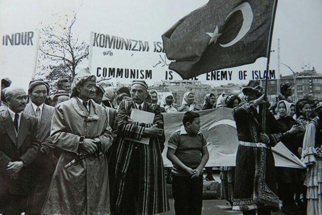 Alptekin, tenant un livre, dirige une manifestation de soutien au séparatisme du Turkestan oriental en 1966. Alptekin se tient devant une banderole qui dit: «Le communisme est l'ennemi de l'islam».