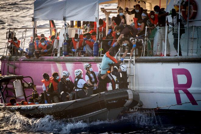 Des migrants recueillis par le « Louise-Michel » sont transférés vers le « Sea-Watch 4 ». © AFP