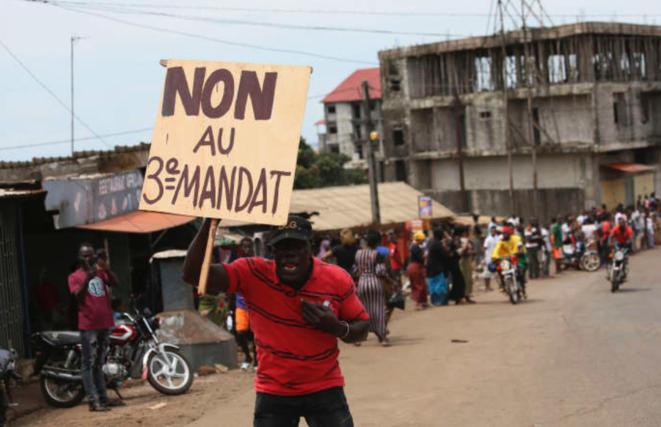 Un homme brandit une pancarte pendant la manifestation contre Alpha Condé jeudi 24 octobre 2019 à Conakry © Youssouf Bah AP