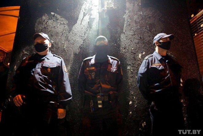 les policiers qui gardent un mur couvert de bitume au milieu de la fête de la cour © onlner