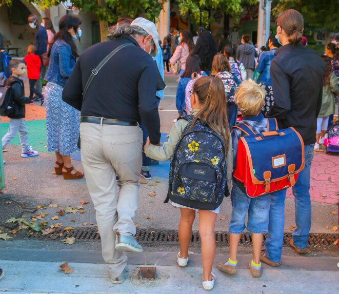 Deux pères portant un masque sur le visage accompagnent leur enfant dans la cour de l'école à Valence le 1er septembre. © Nicolas Guyonnet / Hans Lucas / Hans Lucas via AFP