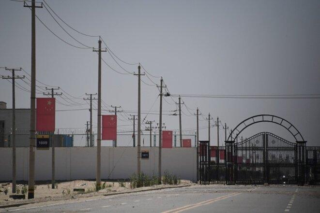 Des drapeaux chinois bordent une route menant à une installation considérée comme un camp de rééducation, où des minorités ethniques musulmanes sont détenues, à la périphérie de Hotan, dans le Xinjiang. Photo : AFP