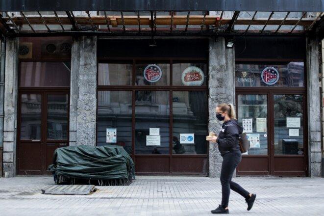 Une passante devant un bar fermé de Bruxelles le 8 octobre 2020. © Kenzo Tribouillard/AFP