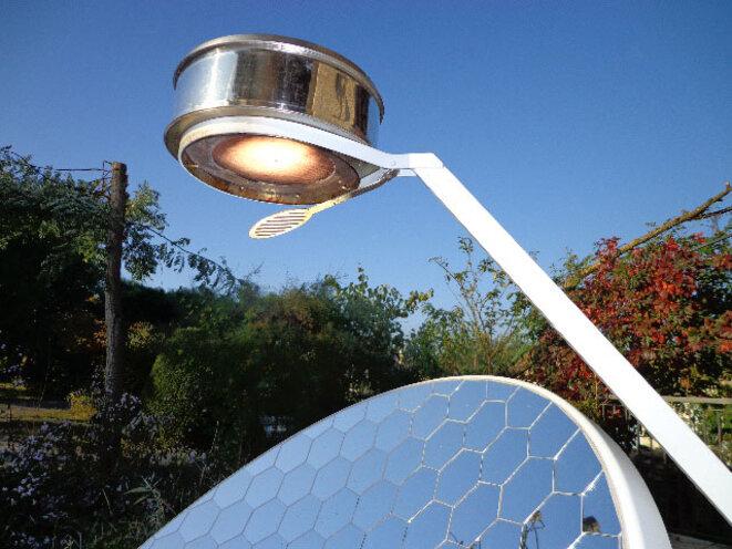Une parabole solaire produit de la chaleur en concentrant les rayons du soleil sur un récipient.