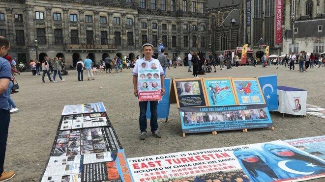 Abdurehim Gheni manifeste avec des photos de ses proches et d'autres Ouïghours disparus, sur la place du Dam à Amsterdam en juillet. (Photo reproduite avec l'aimable autorisation de Abdurehim Gheni)